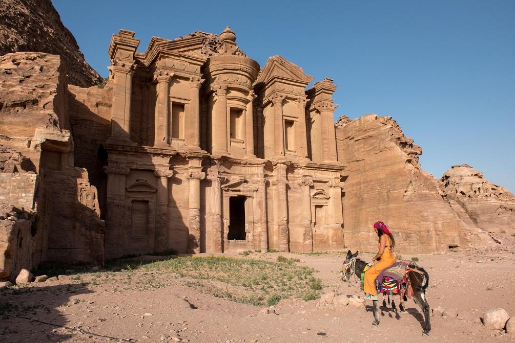 Traveler woman riding donkey in Petra, Jordan